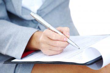 woman write by pen on paper